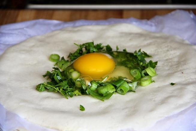 שוברים את הביצה לתוך 'קן' עשבי תיבול. צילום: קרן ביטון כהן