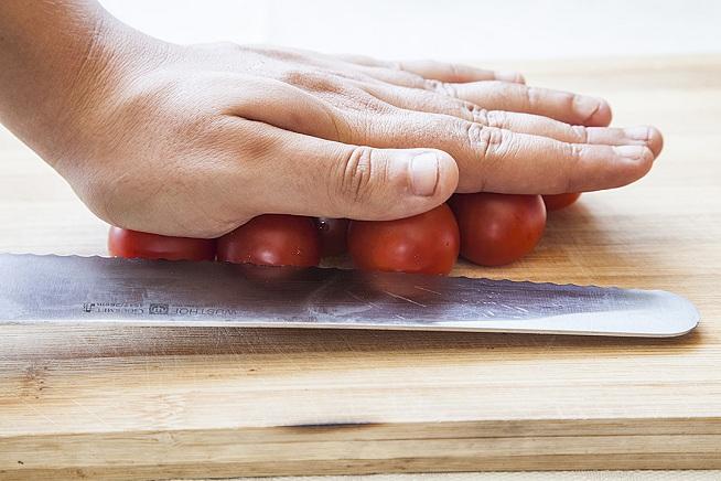 מניחים את עגבניות הרי על קרש, מהדקים עם היד וחוצים בתנועה אחת. צילום: אסף אמברם