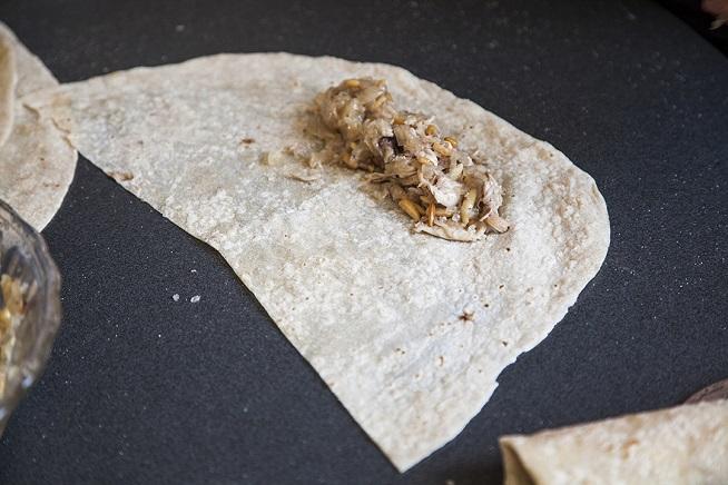 על חצי פיתה דרוזית מניחים שורה מתערובת המילוי. צילום: אסף אמברם