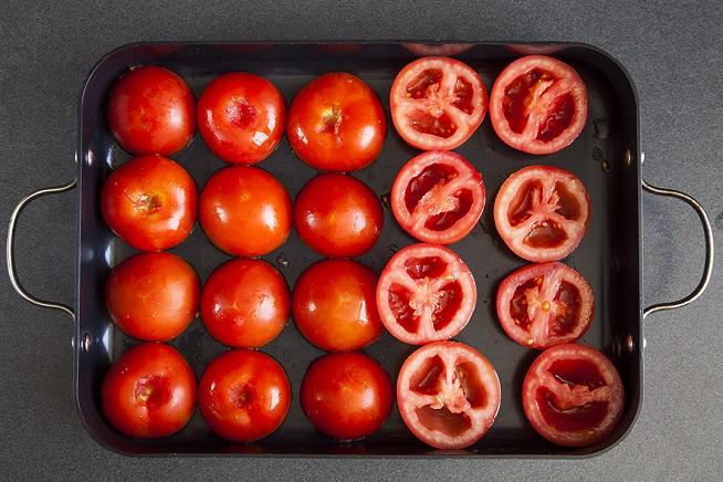 חוצים את העגבניות, מוציאים את הזרעים, ומניחים עם הצד החתוך כלפי התבנית. צילום: אסף אמברם