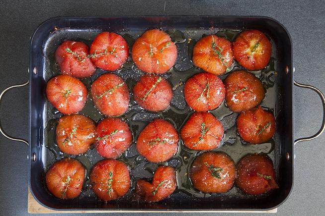 מפזים על העגבניות עלי טימין, מתבלים במלח ושמן זית, ושולחים לתנור סיבוב נוסף. צילום: אסף אמברם