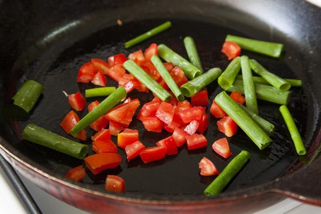 ובמקביל עובדים על המנה הסופית: מקפיצים קוביות עגבניה ובצל ירוק. צילום: אסף אמברם