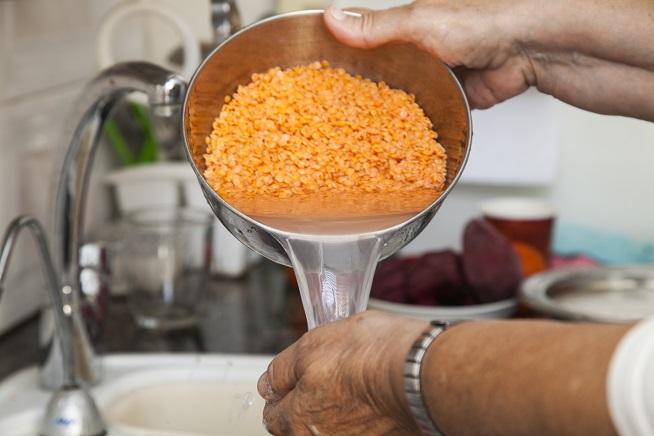 שוטפים את העדשים בקערה עד שהמי השטיפה צלולים. צילום: אסף אמברם
