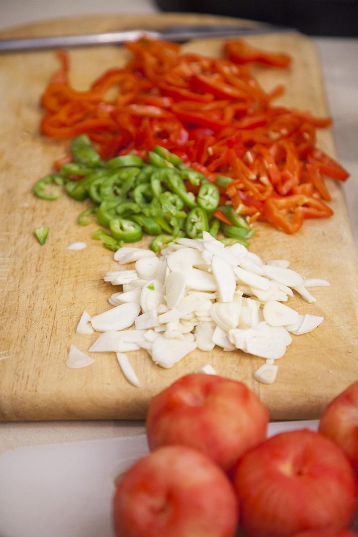 מסדר המטבוחה: עגבניות קלופות, ראש שום שלם פרוס, פלפל ירוק חריף ופלפלים אדומים פרוסים. צילום: אסף אמברם