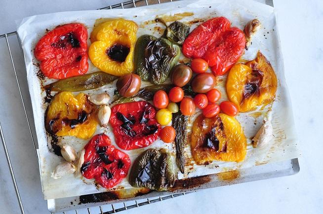 אחרי חצי שעה בתנור זורקים פנימה עגבניות שרי ושיני שום, וממשיכים לאפות 10 דקות או עד שהפלפלים נראים כך. צילום: רות אופק