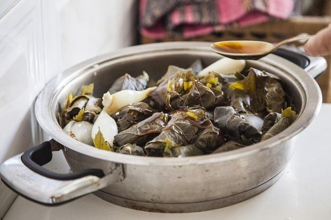 כשהסיר מלא בבצלים ועלים, נותנים בו סילאן ושמן. צילום: אסף אמברם