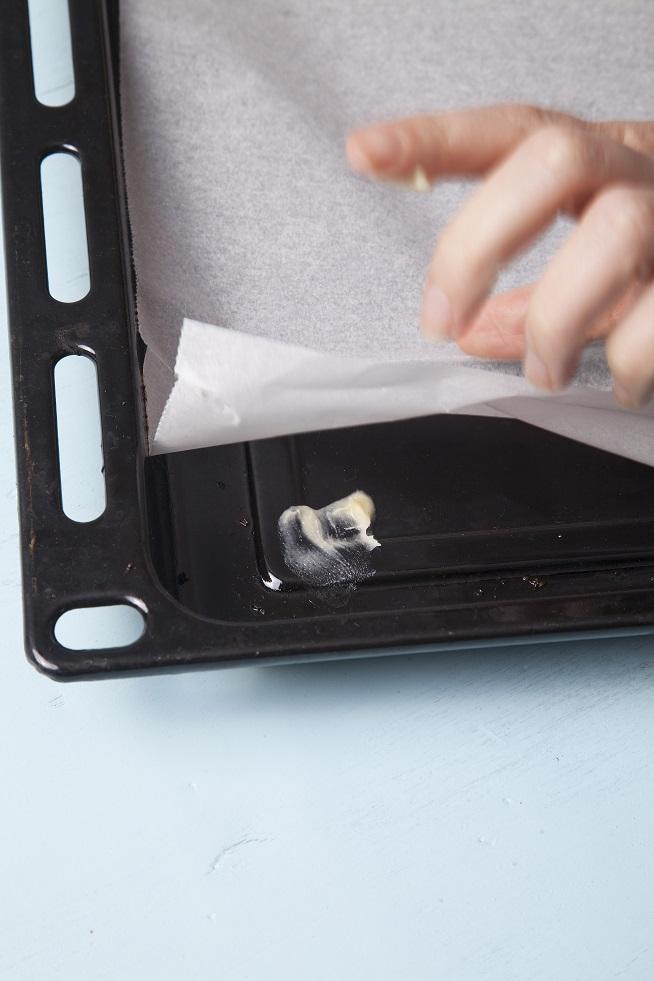 מדביקים את פינות נייר האפייה עם מעט בצק, ככה הוא לא יתרומם לכם בצורה מעצבנת אחרי כל זילוף. צילום: אסף אמברם