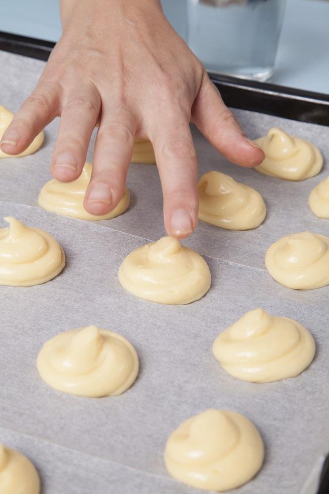 השפיצים של הבצק נשרפים בתנור, אז טובלים אצבע במים (רואים את הכוס במעל התמונה? ) ופוחסים (איזה מילה יפה!) את השפיצים בעדינות. צילום: אסף אמברם