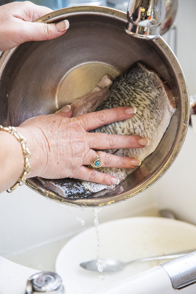 שוטפים את הדגים מהמלח והלימון. צילום: אסף אמברם
